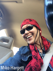 selfie of asian woman in drivers seat smiling at dashboard.